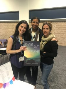 Jennifer Elise Foerster and colleagues stop by the booth to proudly pose with a poster of her most recent collection.